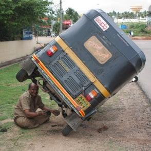 Человек чинит наклоненный на 45 градусов автомобиль
